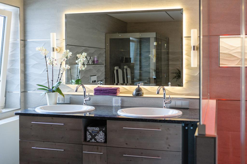 Natursteinwand mit Beleuchtung hinterm Spiegel