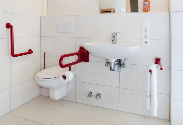 Badezimmer mit roten Stützen am WC für Rollstuhlfahrer und Menschen die Probleme beim Aufstehen haben