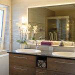 Badezimmer mit Natursteinwänden, einem großen Spiegel in der Mitte von 2 Waschbecken, eine Orchidee ist links neben dem linken Waschbecken
